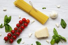 Set of ingredients for cooking italian pasta on a white wooden background, top view. Flat lay Royalty Free Stock Photo