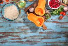 Set of ingredients for making healthy vegetarian. Food on a wooden table. Pumpkin, cranberries, onions, garlic, rice, parsley, oil and tomatoes on a wooden Stock Photography