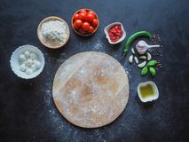 A set of ingredients for pizza and a wooden cutting board for copy space. The view from the top. royalty free stock images