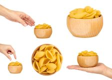Set of Italian raw pasta in wooden bowl. Woman hands, isolated on white background stock photo