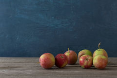Set jabłka na drewnianym stole na błękitnym tle Zdjęcia Stock