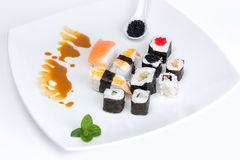 Sushi on a White Plate. Japan Traditional Food. Set of Japanese sushi on a white plate. Hosomaki, uramaki, nigiri and futomaki Royalty Free Stock Photo