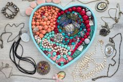 A set of jewelry for women on a wooden tray in the shape of a heart. The view from the top. The concept of fashion and design Valentine`s day Royalty Free Stock Image
