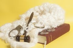 Set for judge:judge wig,handclufs, judge gavel,book end eyeglass. Es on yellow background stock image