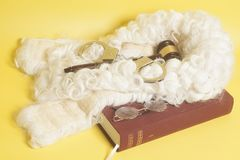 Set for judge:judge wig,handcuffs, judge gavel,book end eyeglass. Es on yellow background stock photo