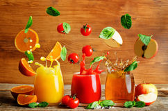 Set of juices: orange, tomato and apple  with flying slices Royalty Free Stock Image