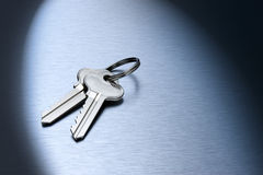 Set Keys Keyring Background. A set of silver keys on a brushed steel background with a spot light Royalty Free Stock Photos