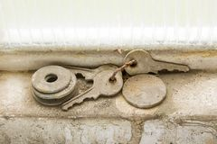 Lost keys. A set of keys were forgotten in the frame of a window of a garage next to washers and old coins, we can see that they have been in this site for a Royalty Free Stock Photo