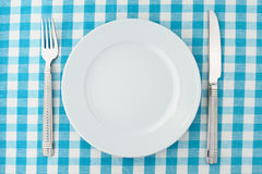Set of kitchen object. Empty dinner plate with fork and knife on blue and white checked gingham tablecloth Royalty Free Stock Photos