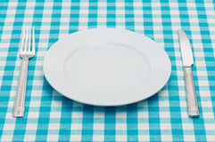 Set of kitchen object. Empty dinner plate with fork and knife on blue and white checked gingham tablecloth Royalty Free Stock Image