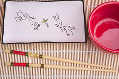Set kitchen for sushi. Chopsticks, a red cup and a plate for sushi, the top view Royalty Free Stock Image