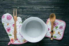Set of kitchen textile, utensils and a pot on dark grey wooden background Stock Photos
