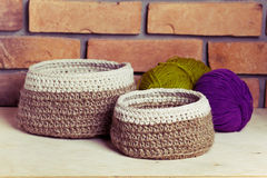 Set of knitted baskets. On brick background Stock Photos