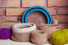Set of knitted baskets. On brick background Stock Photography