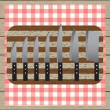 Set of knives. Chopping board. Table-napkin. Wooden table. Top v Royalty Free Stock Photography