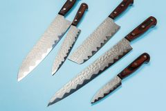 Several different used stainless steel kitchen knives with brown wooden handles stock photo