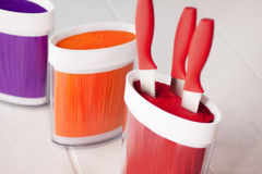 Set of knives with a red handle. In the red stand standing next to the orange and purple Stands for knives Royalty Free Stock Photography