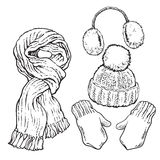 Set of knotted scarf, hat, ear muffs and mittens Royalty Free Stock Photo