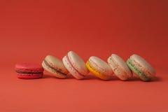 Set kolorowi macaroons brogujący na horyzontalnej linii w czerwonym pastelowym tle Fotografia Stock