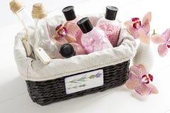 Set kosmetyki dla ciało opieki w łozinowym koszu na białym stole Obrazy Stock