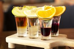 A set of layered cocktails in glasses shooters with fruit as a snack for stock photography