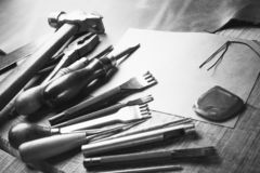 Set of leather craft tools on wooden background. Workplace for shoemaker. Piece of hide and working handmade tools on a work table stock images