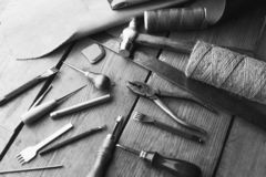 Set of leather craft tools on wooden background. Workplace for shoemaker. Piece of hide and working handmade tools on a work table royalty free stock photos