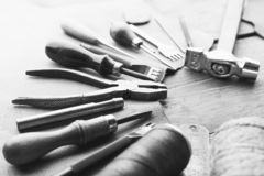 Set of leather craft tools on wooden background. Workplace for shoemaker. Piece of hide and working handmade tools on a work table royalty free stock photography
