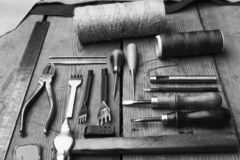 Set of leather craft tools on wooden background. Workplace for shoemaker. Piece of hide and working handmade tools on a work table stock image