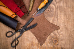 Set of leather craft tools on wooden background. Workplace for shoemaker. royalty free stock images