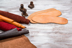 Set of leather in rolls, craft tools on white wooden background. Workplace for shoemaker. Working handmade tools on a work table. Stock Image