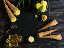 Set of lemon sorbet and accessories. above view.. Top view of lemon ice cream and set of accessories and ingredients on a wooden background with black board for royalty free stock photography