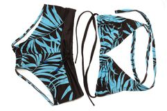 A set of light blue and black colored ladies swimming shorts and trikini with leaf patterns. A photo taken on a set of light blue and black colored ladies Royalty Free Stock Photography