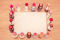 Set of lipsticks around blank card to add text. Makeup and cosmetics: set of lipsticks with white card Stock Photos