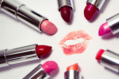 Set of lipsticks around lips mark. Set of many colors of listicks in circle around lipstick kiss mark Royalty Free Stock Photos