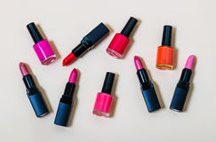 Set of lipsticks and nail polishes on beige background. Set of multicolored lipsticks and nail polishes on beige background Stock Image