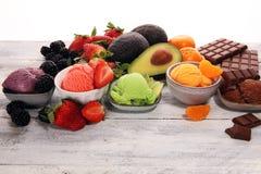 Set lody miarki różni kolory i smaki z jagodami, czekoladą i owoc, fotografia stock