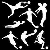 Raster set of silhouettes of football player with a ball on a black background. Set of logo for football, white silhouettes of football players Royalty Free Stock Image