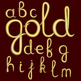 A set of lowercase Latin letters made of thick golden cream. Royalty Free Stock Photography