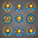 Set of luxury gold cups. Set of luxury golden champion cups, medals, emblems with gold laurel wreaths, blue ribbons for page, web design. Filigree elements Stock Image