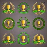 Set of luxury gold cups. Set of luxury golden champion cups, medals, emblems with gold laurel wreaths, green ribbons for page, web design. Filigree elements Stock Photos