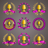 Set of luxury gold cups. Set of luxury golden champion cups, medals, emblems with gold laurel wreaths, purple ribbons for page, web design. Filigree elements Stock Image