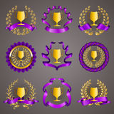 Set of luxury gold cups. Set of luxury golden champion cups, medals, emblems with gold laurel wreaths, purple ribbons for page, web design. Filigree elements Stock Photo