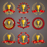 Set of luxury gold cups. Set of luxury golden champion cups, medals, emblems with gold laurel wreaths, red ribbons for page, web design. Filigree elements, icons Stock Photo