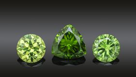 Set of luxury green transparent sparkling gemstones of various cut shape demantoids collage isolated on black background royalty free stock image