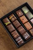 Set of luxury handmade bonbons in a gift box on wooden backgroun stock photography