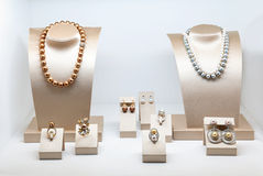 Set of luxury jewelry with precious gems and diamonds. Necklaces made of natural pearls on a stands. Women accessories. Royalty Free Stock Images
