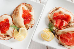 Set of luxury pancakes with seafood top view. Set of luxury pancakes with seafood. Top view on white plates. Russian traditional salty crepes with seafood Royalty Free Stock Photo