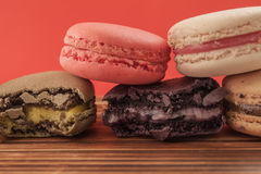 Set of macarons in various colors on wood table in red pastel is Stock Photography
