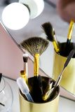 A set of makeup artist brushes for professional makeup on a white table in front of the mirror in the beauty salon, the Concept of stock images
